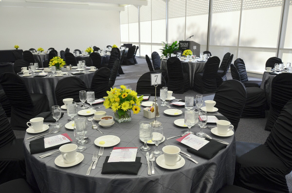 Several grey linen covered tables and black linen covered chairs with crystalware, porcelain plates, and silverware and yellow flower centerpieces.